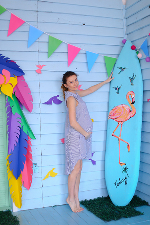 Young pregnant woman standing near surfboard and decorated children house. Concept of pregnance and motherhood, summer.