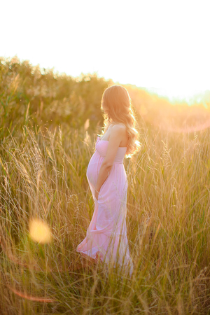 Pregnant woman standing in sun rays with steppe background, wearing pink dress. Concept of gentle summer photo session and pregnance.