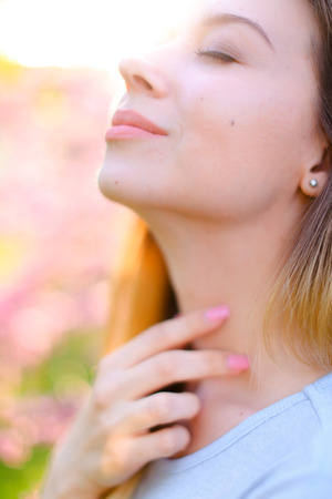 Close up face of young girl in pink blossom background. Concept of breathing fresh air and beauty.