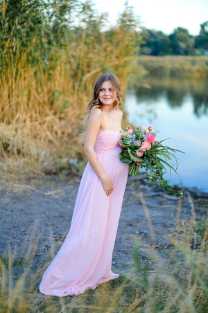 Pregnant young woman wearing pink dress with bouquet of flowers standing near lake. Concept of gentle photo session and pregnance.