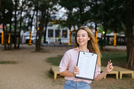 Young girl standing with paper document on resort, keeping pen. Concept of cheap tickets and successful visa application.