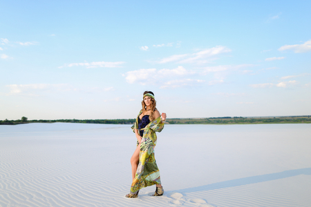 Young female person wearing swimsuit and green beach robe standing on sand. Concept of desert photo session and relaxing on nature. Standard-Bild
