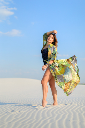 Young woman wearing green beach robe standing on white sand in desert. Concept of summer photo session and fashion. Standard-Bild