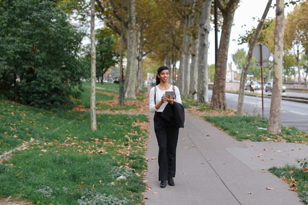 Afro american female student walking with tablet in autumn park, wearing backpack. Concept of modern gadget and stylish black students Imagens