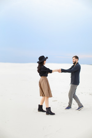 Young girl wearing skirt nad hat holding hands of handsome man on snow in white background. Concept of feeling and romantic photo session. Zdjęcie Seryjne
