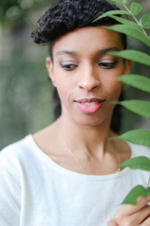 Close up face of black half american nigerian woman keeping green leaf, having bangs and wearing white blouse. Concept of natural beauty. 写真素材