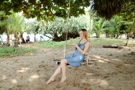 Young european woman riding swing and using smatrphone, sand and tree in background. Concept of summer vacations on tropical and exotic resort, modern technology.