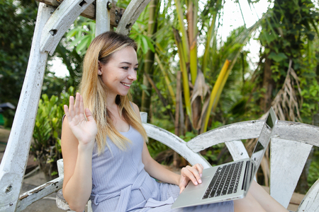 Young female person making video call by laptop adn sitting in palms and exotic plants in background. Concept of summer tropical vacations and modern technology. Stockfoto