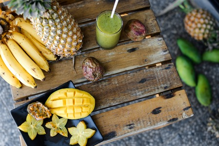 Carambola with mango in plate near bananas and pine-apple on wooden table. Concept of exotic fruits and tropical healthy food.