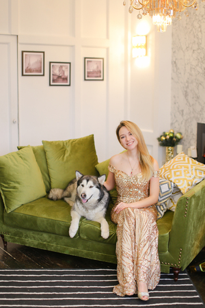 Young nice woman wearing dress sitting on sofa in living room with husky. Concept of pets, celebrating holidays, fashion and interior.
