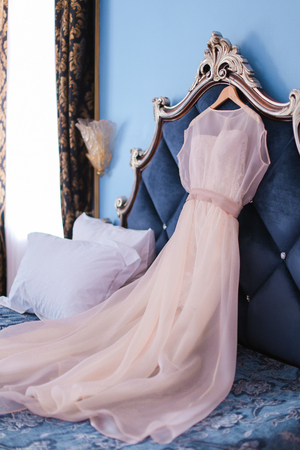Bridal dress on bed. Concept of wedding clothes and fashion. Stock Photo