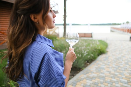 Happy woman drinking white wine on backyard and resting. Concept of spending weekends and summer vacations.