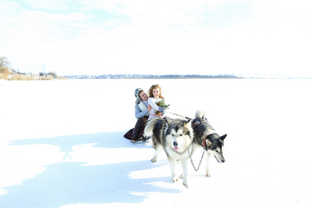 Happy woman and man sledging with huskies on snow. Concept of romantic winter photo session and Alaskan vacations. Archivio Fotografico - 103410825
