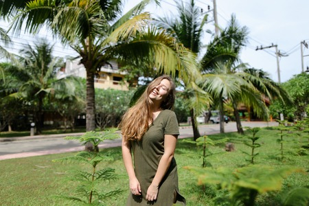 Young woman wearing khaki dress and standing near palms in background. Conept of resting in Florida and summer exotic vacations.