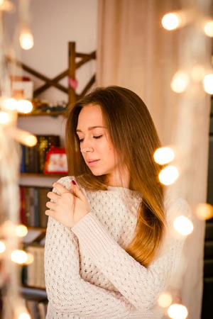 Young woman standing near yellow twinkling garlands in room. Concept of celebrating New Year and Christmas.