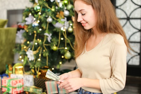 blogger making composition of presents for photo, young woman sitting on carpet near decorated pinetree. Pretty fair-haired female wearing beige T-shirt and jeans smiling. Concept of New Year sales, blogging or gift wrapping.
