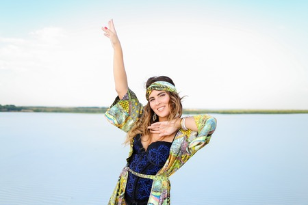 Caucasian young woman with raised hand wearing black swimsuit and green beach robe standing on sand. Concept of summer clothes collection and fashion. Standard-Bild