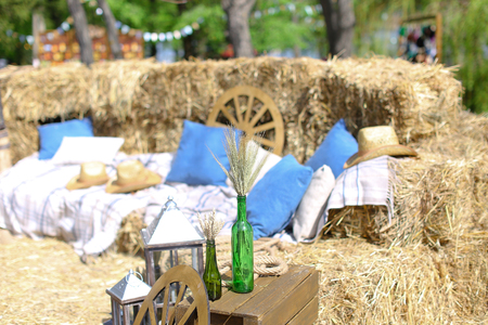 Wooden wheel with blue pillows, hats and bottles with wheat ears. Concept of summer vacations on farmland.