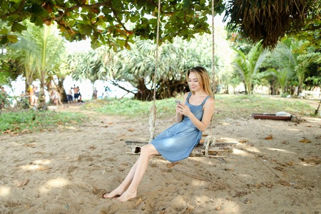 Young woman riding swing and using smatrphone, sand and tree in background. Concept of summer vacations on tropical and exotic resort, modern technology.