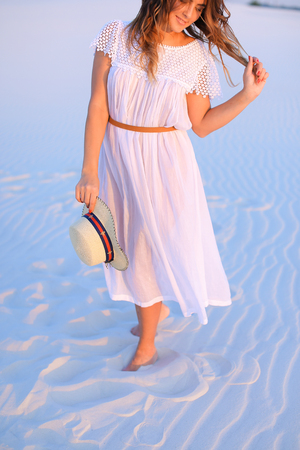 Smiling woman wearing dress and hat standing on white sand in blue background. Concept of resting on beach and summer seasonal photo session.