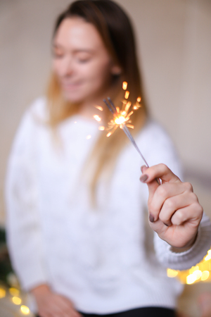 Blurred photo of young smiling woman with closeup bengal light near twinkling yellow garlands. Concept of handmade decorations for Christmas and New Year holidays.