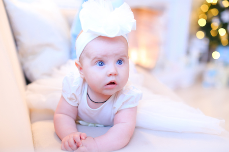 Little female baby with blue eyes lying on sofa and wearing white clothes. Concept of cute children. Stock Photo