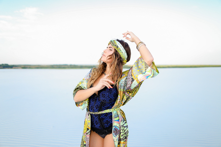Caucasian pretty woman with raised hand wearing black swimsuit and green beach robe standing on sand. Concept of summer clothes collection and fashion.