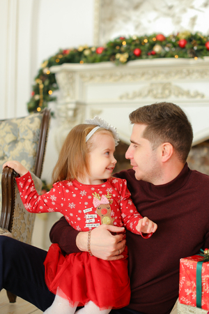 European father sitting with little daughter near decorated fireplace and keeping presents. Concept of celebrating Christmas and parent with child.