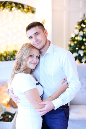 Young woman hugging man wearing white shirt, decorated room for Christmas in background. Concept of happy couple and New Year atmosphere. Imagens