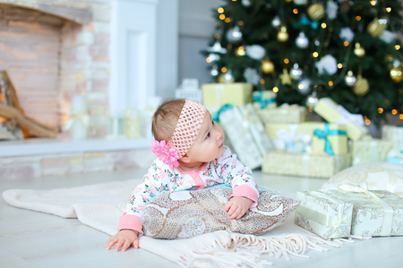 Pretty female baby lying on floor near twinkling Christmas tree and presents. Concept of New Year photo session for kid. Stock Photo