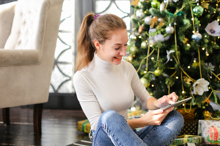 architect using tablet, smiling female laying on carpet near decorated pinetree watching photos in social networks. Pretty smiling girl with ponytail wearing white turtleneck jeans spending free time in cozy room with grey chair green sofa. Concept of innovative technologies, gadgets and Internet. Stock Photo