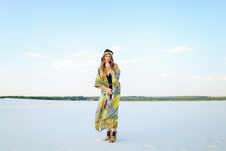 Young female person wearing green beach robe and black swimsuit standing on sand. Concpt of summer fashion clothes collection and vogue, photo session n desert.