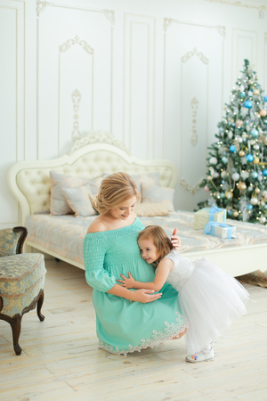 Pregnant european woman wearing blue dress hugging belly and sitting with little daughter near Christmas tree in bedroom. Concept of winter holidays and waiting for child.