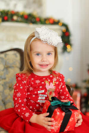 Little blonde girl wearing red dress, keeping gift and sitting on sofa near decorated fireplace. Concept of childhood and celebrating Christmas with presents.