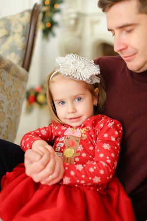 Little girl sitting with father and wearing red dress. Concept of winter holidays atmosphere and happy family members. Stock Photo