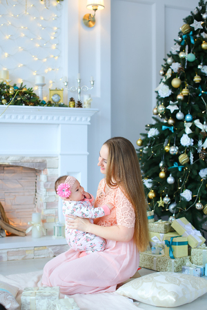 Young ptretty mother holding daughter in arms near decorated fireplace and Christmas tree, wearing pink dress. Concept of celebrating winter holidays and motherhood. Stockfoto