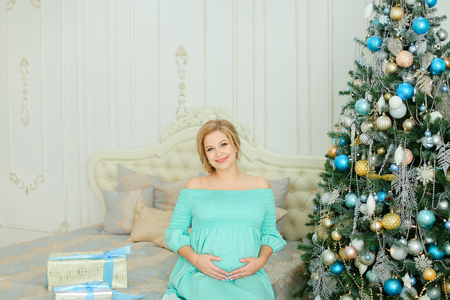 Pregnant woman wearing blue dress hugging belly and sitting near Christmas tree and presents. Concept of winter holidays and waiting for child.