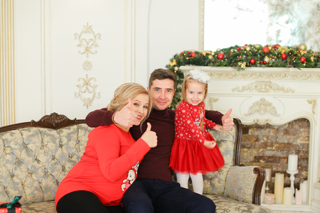 Beautiful pregnant female person sitting with husband and daughter near Christmas tree and decorated fireplace. Concept of happy family and celebrating winter holidays.