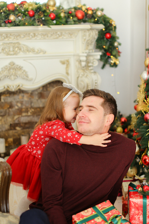 Smiling father sittling with little daughter near decorated fireplace and Christmas tree, keeping presents. Concept of celebrating New Year and winter holidays, happy parent with child. Banque d'images