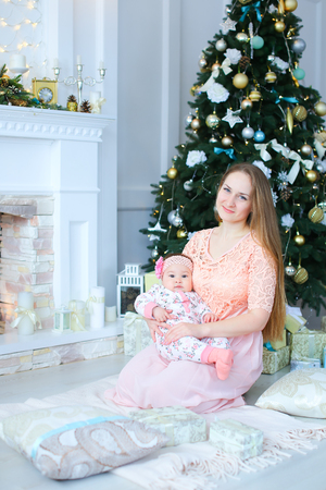 Happy caucasian woman gifting little daughter presetn near decorated fireplace. Concept of celebrating winter holidays and playing with baby.