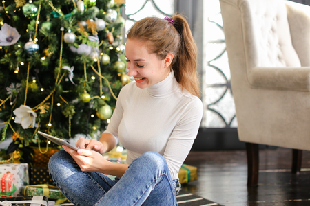 architect using tablet, smiling female laying on carpet near decorated pinetree watching photos in social networks. Pretty smiling girl with ponytail wearing white turtleneck jeans spending free time in cozy room with grey chair green sofa. Concept of innovative technologies, gadgets and Internet. Banque d'images