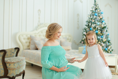 Pregnant happy woman wearing blue dress hugging belly and sitting with little daughter near Christmas tree in bedroom. Concept of winter holidays and waiting for child.