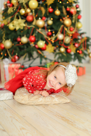 Little female girl lying on floor near Christmas tree and cute gifts. Concept of childhood and winter holidays inspiration.