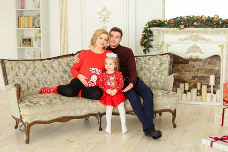 Caucasian father and pregnant mother sitting with little daughter on sofa near decorated fireplace. Concept of happy european family. Banque d'images
