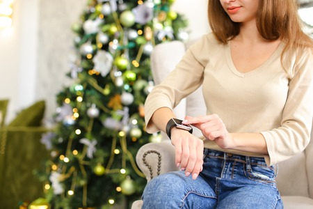 girlfriend get smartwatch from boyfriend as present for New Year, smiling lady sitting in chair near pinetree with gift on hand. Fair-haired girl with neat manicure wearing everyday clothes. Concept of gadgets, innovative technologies or holiday sales. Stock Photo