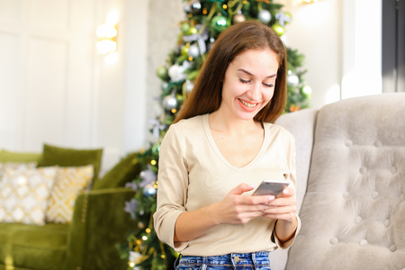 architect using tablet, smiling female laying on carpet near decorated pinetree watching photos in social networks. Stock Photo