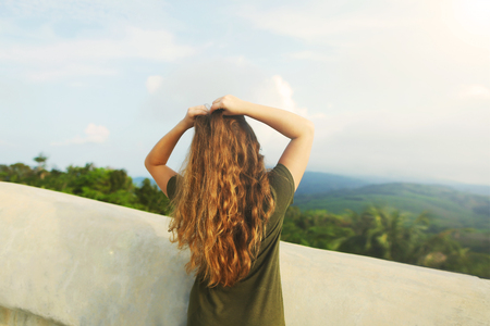 Back view of young girl with raised hands wearing khaki dress, standing in mountains background. Concept of summer vacations and resting on nature.