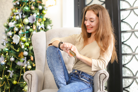 girlfriend get smartwatch from boyfriend as present for New Year, smiling lady sitting in chair near pinetree with gift on hand. Fair-haired girl with neat manicure wearing everyday clothes. Concept of gadgets, innovative technologies or holiday sales.