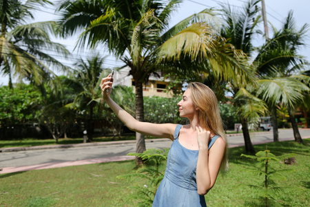 Young blonde girl making selfie by smartphone with palms in background. Concept of exotic summer vacations and modern technology.