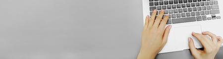 Banner de sitio web del teclado de la computadora portátil de vista superior y manos femeninas con copyspace en fondo de color gris. Concepto de ocupación de encabezado y redactor de blog, negocios.